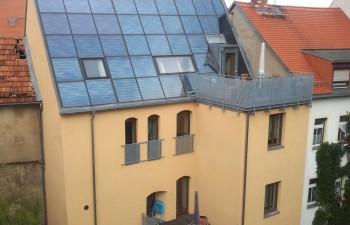 ENERGETIKhaus100® historio - das Solarhaus in Freiberg mit Blick auf die Kollektorfläche, die Dachterrasse und den Balkon