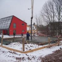 22.02.2013: Während die Betonlage der Bodenplatte für den Massivbau gegossen wird, ist der erneute Wintereinbruch keinen Fußtritt entfernt.