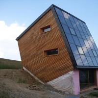 10. Juli 2010: Das Gerüst ist gefallen und der ENERGETIK- Cube fast fertig gestellt. Erstmals wurde die Kombination aus Sichtbeton und massiver Holzbauweise realisiert. In die Solarthermieanlage wurde zusätzlich ein hochmodernes Fenstersystem integriert. Außerdem verfügt das Gebäude an seiner Südseite über eine attraktive 15m² große Glasfassade. Das Haus im kubischen Design hat eine Stülpschalung aus sägerauen, unbehandelten, einheimischen Hölzern erhalten. Sie verleiht der Fassade einen natürlichen Charakter und fügt sich harmonisch in die reizvolle Landschaft des Erzgebirges ein.