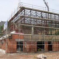 Nachdem die Tragwerkskonstruktion die letzten Wochen frei lag, wird sie nun mit Trapezblechen versehen und so das Dach neu gedeckt.